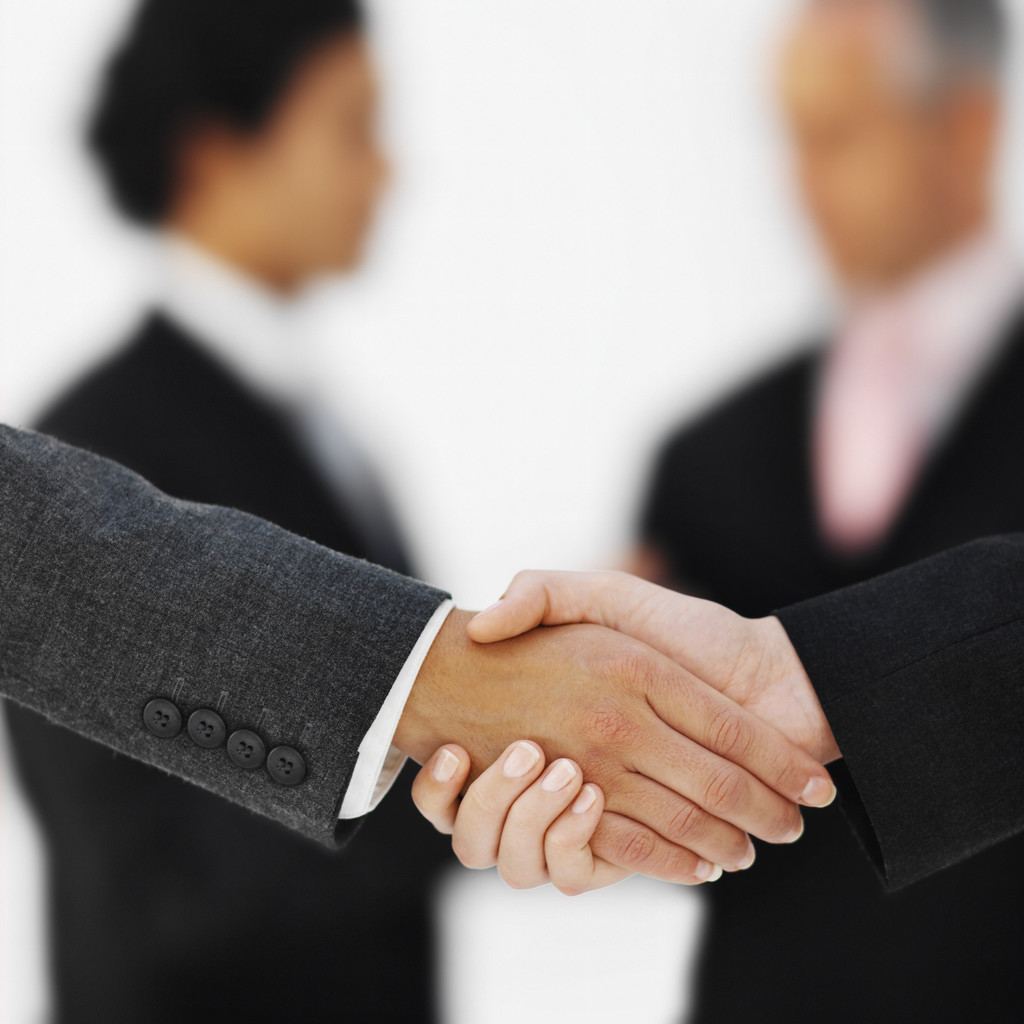 close-up-of-the-hands-of-two-businesswomen-shaking-hands-with-two-businessmen-in-background-5